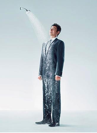 Tipo con traje en la ducha
